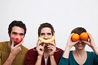 Men and women holding fruits in front of face