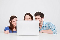 Man and women using laptop, smiling