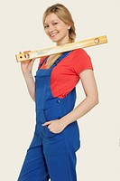 Young woman holding spirit level, smiling, portrait