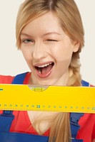 Young woman holding spirit level, winking, close_up