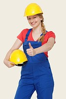 Young woman holding hard hat, showing thumbs up sign, portrait