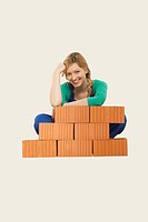Woman sitting behind stack of bricks, smiling, portrait