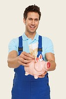 Man putting currency in piggy bank, smiling, close_up, portrait