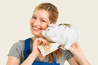 Woman in overall holding euro notes and piggy bank, smiling, portrait
