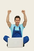 Man in overall sitting with laptop and cheering, portrait