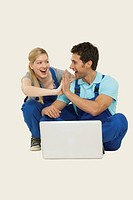 Man and woman in overall using laptop, giving high_five