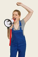 Woman in overall shouting through megaphone