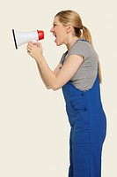 Woman in overall shouting through megaphone, side view