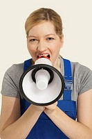 Woman in overall shouting through megaphone, close_up, portrait