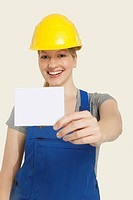 Construction worker wearing hard hat and holding paper, smiling, portrait