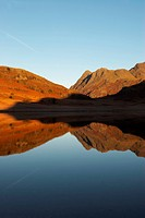 Reflections in Blea Tarn at sunrise. Blea Tarn lies at the top of the pass between Dungeon Ghyll at the head of Great Langdale, and Fell Foot Farm at ...