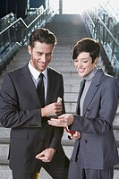 Germany, Bavaria, Munich, Two business people on staircase at underground station, holding mobile phone, smiling, portrait