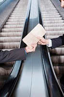 Germany, Bavaria, Munich, Two people on escalator passing documents
