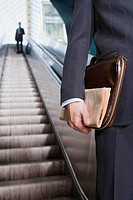 Germany, Bavaria, Munich, Two businessmen on escalator