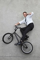 Businessman riding bicycle using cell phone, elevated view