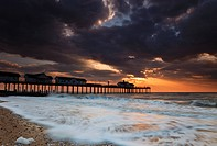 England, Suffolk, Southwold, Storm clouds gather over Southwold pier in Suffolk at dawn.