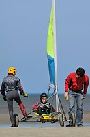 Child with instructor during land sailing / sand yachting / land yachting course on the beach at De Panne, Belgium