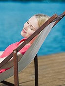 A woman with her eyes closed reclining in a beach chair