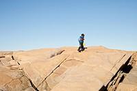 A person hiking over rocks, Bohuslan, Sweden