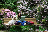 a girl sitting on a park bench with her dog while working on her laptop computer