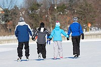 Family ice skating outdoors in winter together