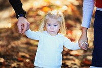 a young girl holding the hands of her parents