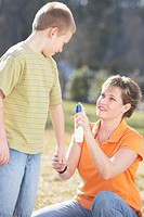 a mother spraying insect repellent on her son