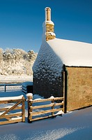 Scotland, Scottish Borders, Ladykirk, The gable end of the Sands Shiel on the River Tweed covered by a winter snowfall.