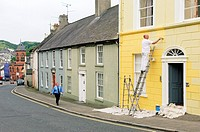 Georgian houses in English Street in the ancient Irish town of Downpatrick lead up to Down Cathedral  Man painting house front