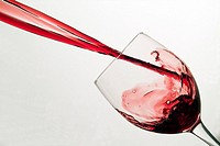 Red wine splashing into wine glass
