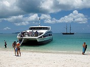 Tourists disembark from the catamaran 'Voyager' on a Barrier Reef island in the Whitsundays  The anchored tall ship in the background is the 127 foot,...