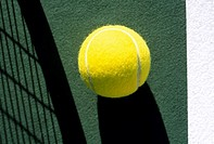 Line and tennis ball on court next to shadow of tennis racket