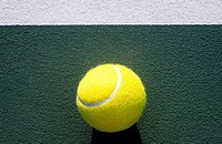Tight shot of tennis ball on court next to line