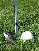 Golf ball in rough about to be hit by iron golf club, tight shot