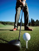 Golfer about to hit golf ball off of tee with driver, low angle