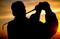 Silhouette of golfer swinging golf club at sunset