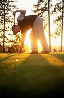 Golfer leaning on driver placing ball on tee with sunlight coming through trees