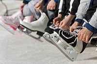 Family lacing up skates outdoors