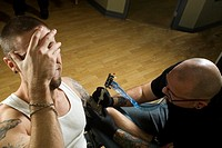 Client in pain getting a tattoo by concentrated tattooer