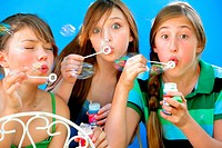 three friends blowing bubbles