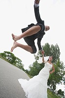 a groom jumping in the air while holding the bride´s hand