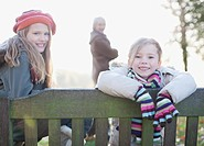 Sisters sitting on bench outdoors in autumn