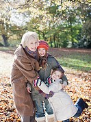 Grandmother hugging granddaughters outdoors in autumn