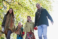 Family holding hands outdoors in autumn