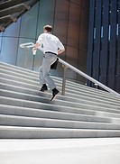 Businessman rushing up steps outdoors (thumbnail)