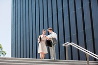 Business people talking at top of steps outdoors