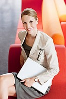 Businesswoman with laptop in waiting area