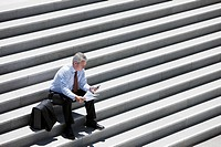 Businessman sitting on outdoor steps and text messaging