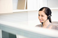 Smiling businesswoman wearing headset in office cubicle