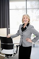 Laughing businesswoman standing in office conference room